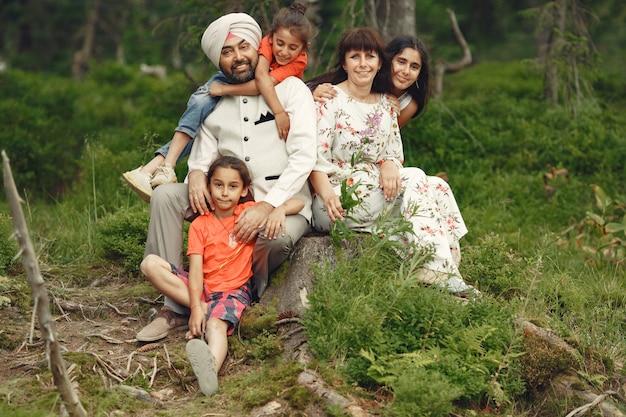 Uomo indiano in una foresta. maschio in un turbante tradizionale. famiglia internazionale in una foresta estiva.