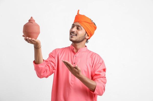 Индийский мужчина держит копилку на белой стене