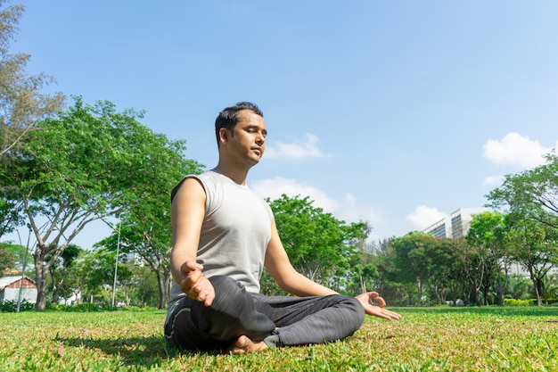 Indian man meditating in lotus pose outdoors on summer lawn with trees in background.