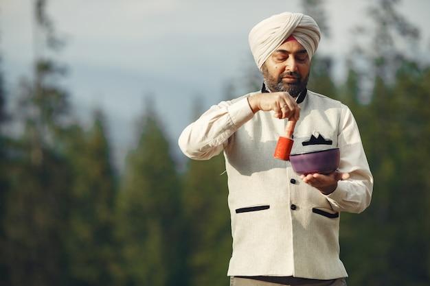 Uomo indiano in montagna. maschio in un turbante tradizionale. induista con cose speciali per i rituali.