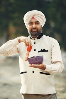 Indian man in a mountains. male in a traditional turban. hinduist with special things for rituals.