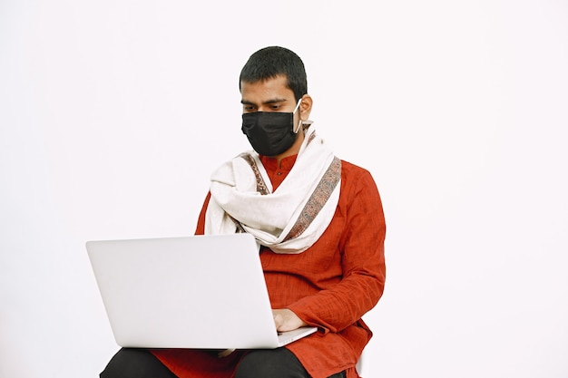 Indian man in national costume working with laptop on a white wall.