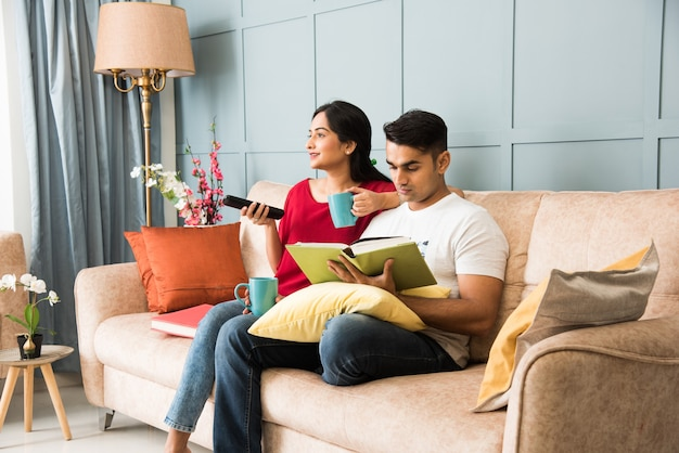 Indian man reading book and wife watching tv while sitting on sofa or couch