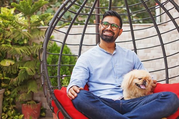 Индийский мужчина сидит на подвесном стуле со своей маленькой собакой