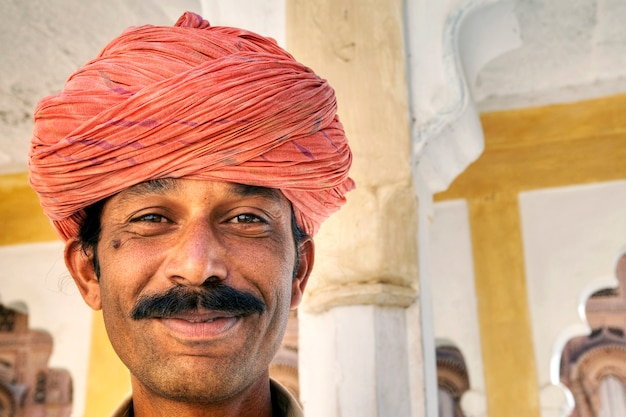 Indian man smiling to the camera.