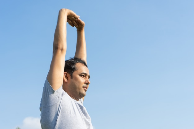 Indian man stretching arms outdoors with blue sky in background. yoga concept.