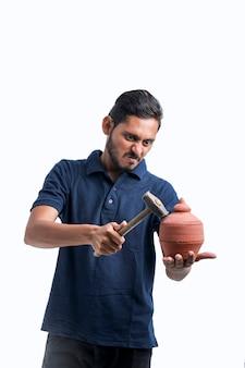 깨진 점토 돼지 저금통에 망치를 사용하는 인도 남자.