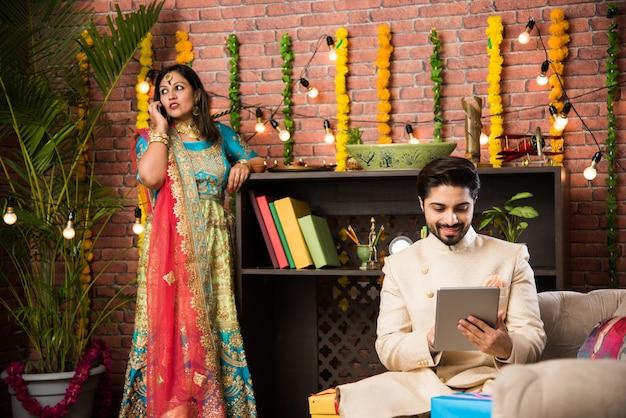 Индийский мужчина использует планшет или планшет с сенсорным экраном компьютера и жена освещает дия на заднем плане в день фестиваля дивали