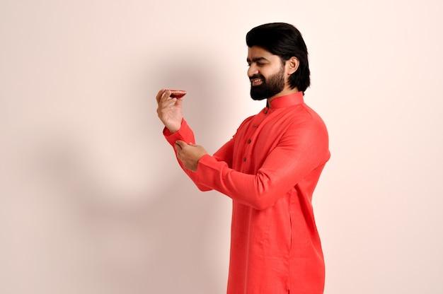 오렌지 쿠르타를 입고 디왈리를 위해 디야를 바라보는 인도 남성