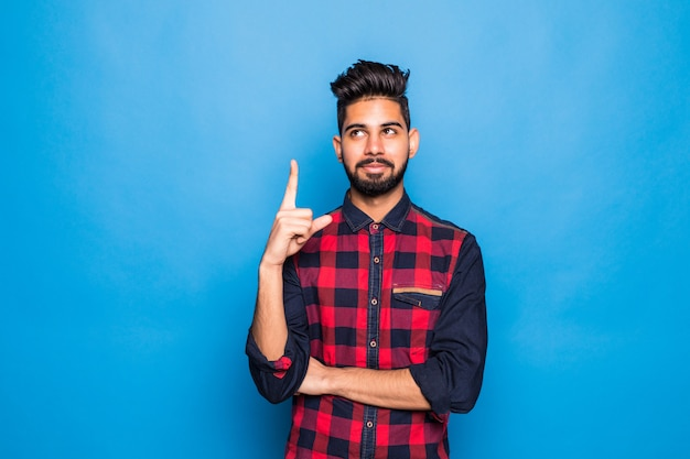 Indian man with beard raising index finger up while having brilliant idea isolated on blue space