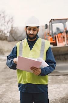 일하는 인도 사람. 노란색 조끼를 입은 남성. 폴더를 가진 남자.