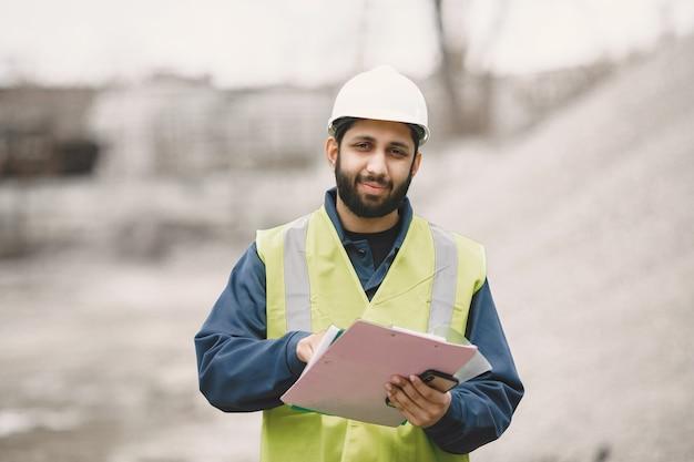 일하는 인도 사람. 노란색 조끼를 입은 남성. 휴대 전화를 가진 남자입니다.