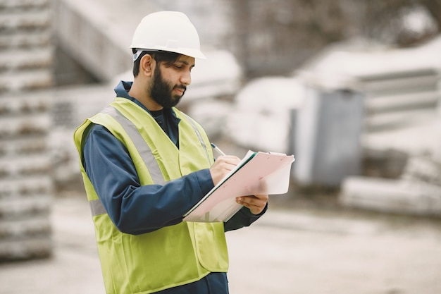 Indian man working. male in a yellow vest. man with folder.