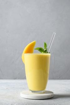 Индийский манго или куркума ласси на сером фоне