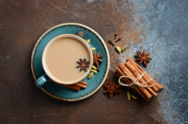 Indian masala chai tea. spiced tea with milk on dark rusty top view, flat lay.