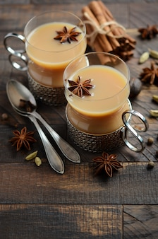 Indian masala chai tea. spiced tea with milk in the vintage cups on the rustic wooden tabl