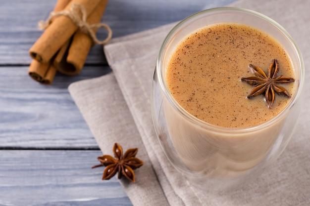 Индийский чай масала со специями, молоком, корицей в стакане. вид сверху