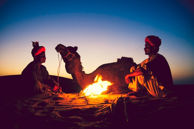 Indian men resting by the bonfire with their camel