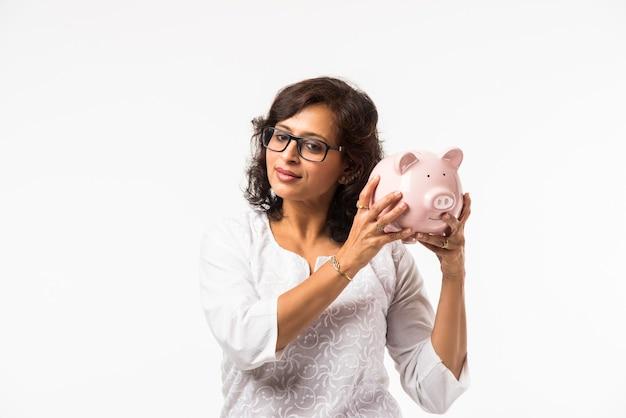 インドの中年女性または貯金箱を持つ女性、白い背景の上に孤立して立っている