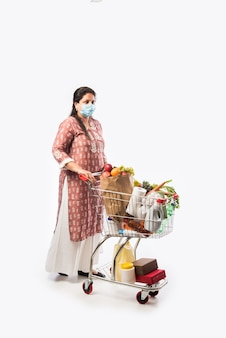 쇼핑 카트 또는 식료품 야채와 과일의 전체 트롤리와 인도 중간 나이 여자는 흰색 배경 위에 전체 길이 사진을 격리