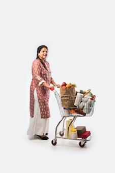 ショッピングカートまたは食料品、野菜、果物でいっぱいのトロリーを持つインドの中年女性。白い壁の上の孤立した全身写真