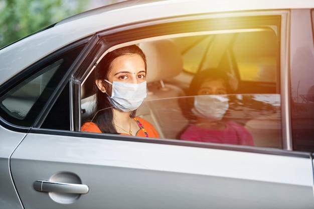 차를 운전하는 동안 안면 마스크 또는 의료 마스크를 착용하는 인도 어머니 딸
