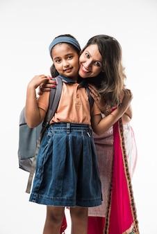 インドの母親は、制服を着た女子高生がお弁当箱、髪型、またはスクールバスを待っている準備をするのを手伝っています