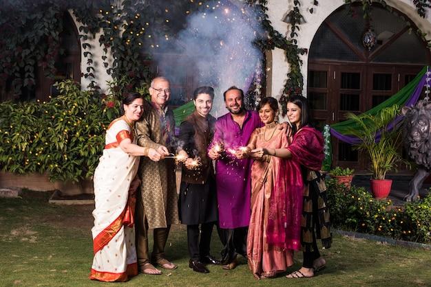 Индийская семья из разных поколений празднует фестиваль дивали, играя с петардами возле дома
