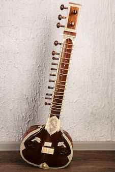 灰色の壁の隣に立っているインドの楽器シタール