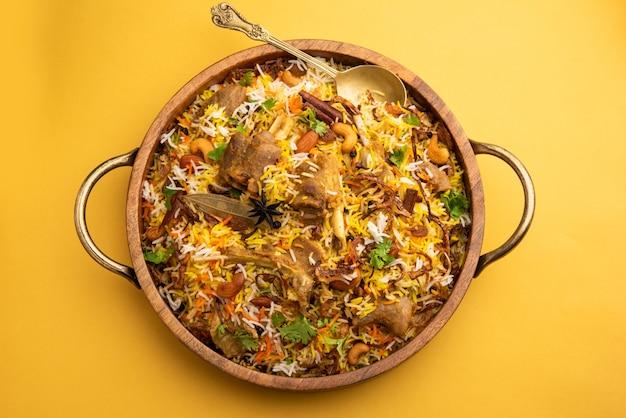 Индийское бирьяни из баранины, приготовленное с рисом басмати, подается с йогуртовым соусом на мрачном фоне, выборочный фокус