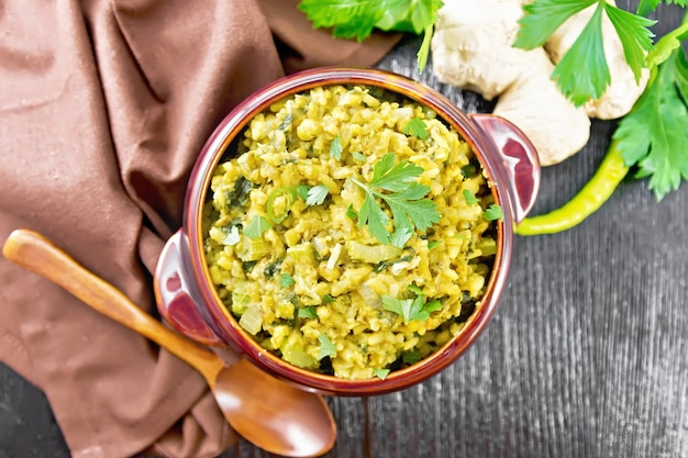 Indian national dish kichari made of mung bean, rice, celery, spinach, hot pepper and spices in a bowl on a towel, ginger and spoon on wooden board background from above