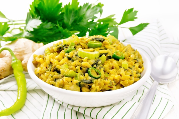 Indian national dish kichari made of mung bean, rice, stalk celery, spinach, hot pepper and spices in a bowl on a napkin, ginger on light wooden board background