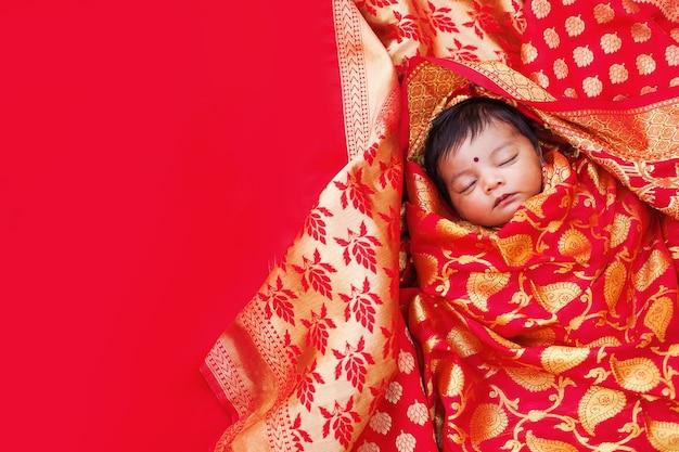 빨간 바나라시 사리에 싸여 자고 있는 인도의 갓난 아기 소녀