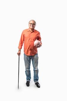 인도 노인 또는 은퇴 한 고위 남성 성인 돼지 저금통 또는 돈 상자를 들고