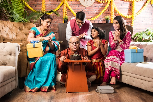Indian old man with family celebrating birthday by blowing candles on cake while wearing ethnic wear