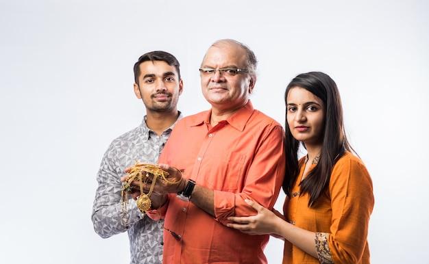 젊은 아들과 딸 또는 금 보석, 장식품을 들고 부부와 함께 인도 노인
