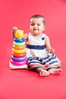 Индийский или азиатский малыш, младенец или младенец, играющий с игрушками или кубиками, лежа или сидя изолированно на ярком или красочном фоне