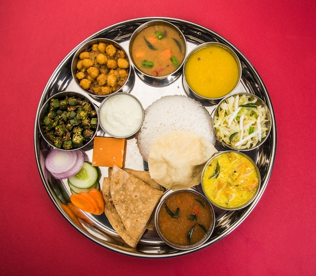 インド料理またはヒンドゥー教のベジターリーまたはレストランスタイルのランチまたはディナー用の完全なフードプラッター。クローズアップ、セレクティブフォーカス