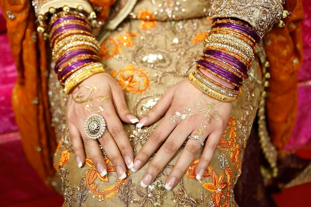 Indian pakistani bride hands with golden henna and jewelry close up