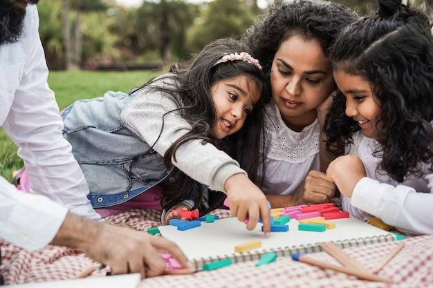 Индийские родители веселятся в городском парке, играя с деревянными игрушками со своей дочерью и сыном - основное внимание уделяется лицу маленькой девочки
