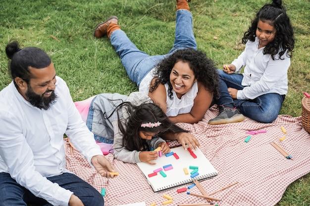 娘と息子と木のおもちゃで遊んで都市公園で楽しんでいるインドの両親-母の顔に主な焦点