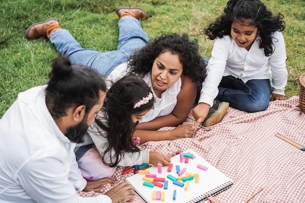 娘と息子と木のおもちゃで遊んで都市公園で楽しんでいるインドの両親