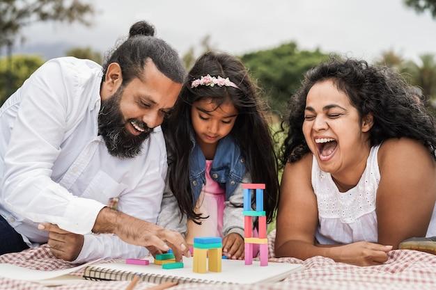 Индийские родители веселятся в городском парке, играя с деревянными игрушками со своей дочерью - основное внимание уделяется лицу матери