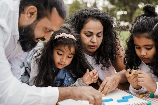 Indian parents having fun at city park playing with wood toys with their daughter and son - focus on mother face
