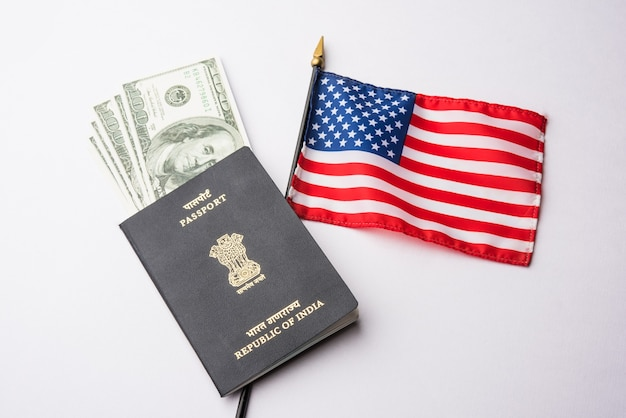 Indian passport with us dollars with american flag in the background, concept showing applying for tourist or h-1b visa