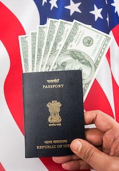 Индийский паспорт с долларами сша с американским флагом на заднем плане, концепция, показывающая подачу заявления на туристическую визу или визу h-1b
