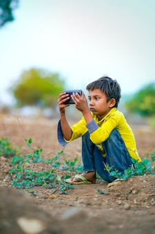 Indian poor child playing with mobile at agriculture field. rural scene.