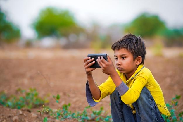 Индийский бедный ребенок, играющий с мобильным телефоном на поле сельского хозяйства. сельская сцена.