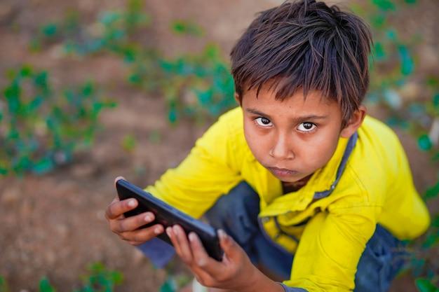 농업 분야에서 모바일 놀고 인도 가난한 아이. 농촌 현장.