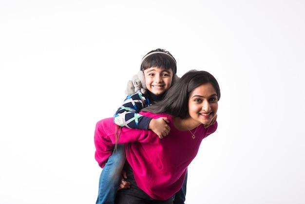 息子とインドのかわいい母親は白い背景に冬の服やセーターを着ています